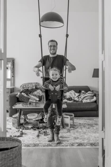 Familienreportage. Kind schaukelt zuhause
